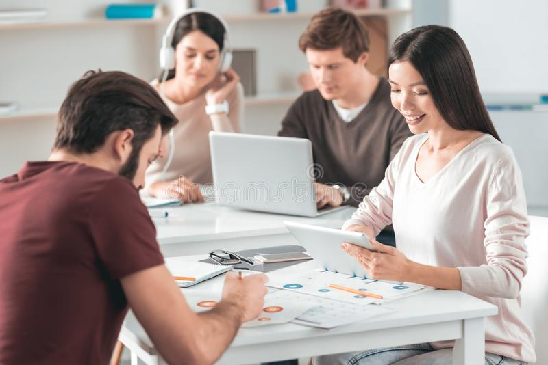 Delighted joyful colleagues working in team. Pleasant cooperation. Delighted joyful colleagues sitting together at the table while working in team royalty free stock image