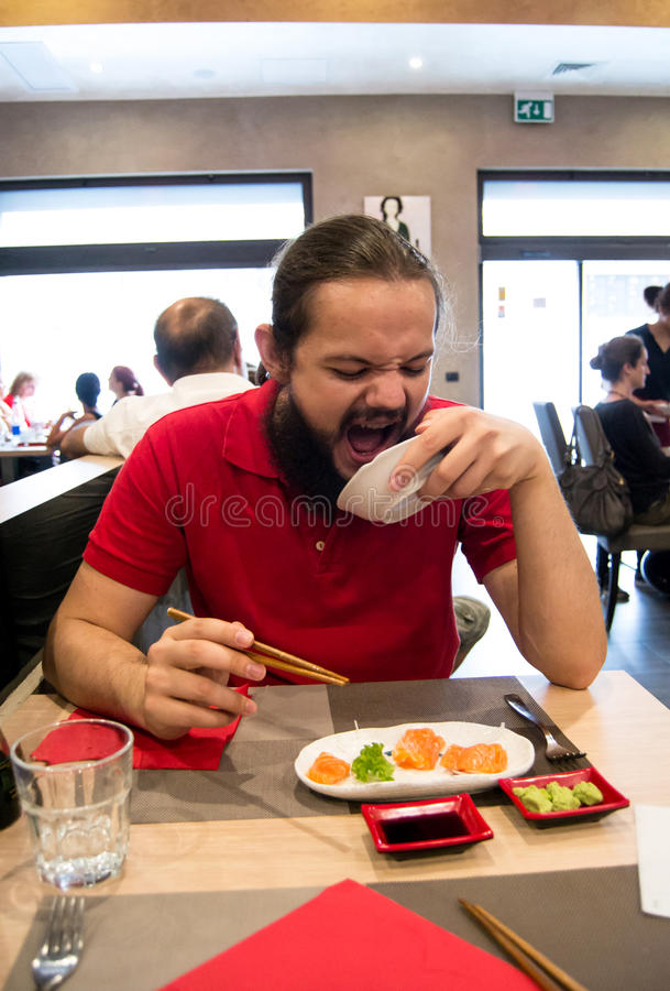 Delighted man / customer in red shirt devouring Chinese / Japanese food in a restaurant. With a mouth wide open stock photography