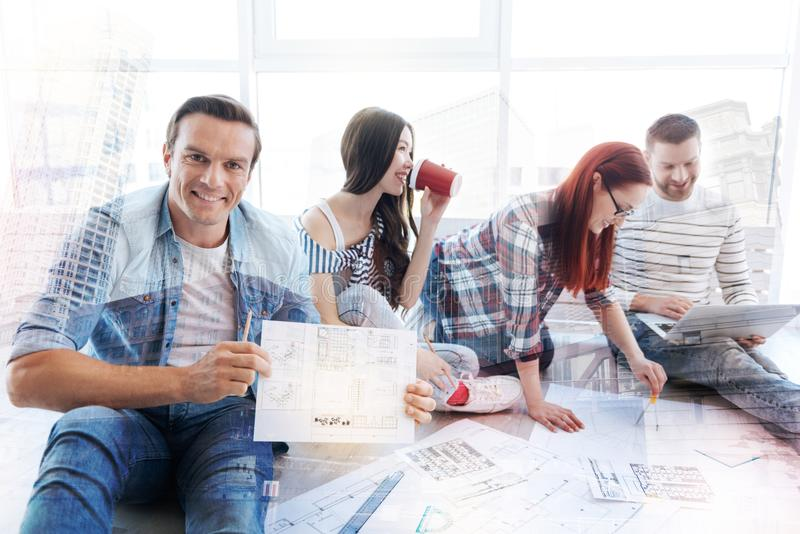 Delighted man showing a sketch to you. Have a look. Delighted men holding a sketch in hand and showing it to you while his colleagues occupied with work royalty free stock image