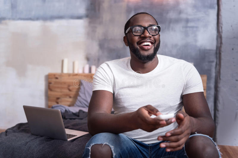 Delighted man watching TV in bedroom royalty free stock photos
