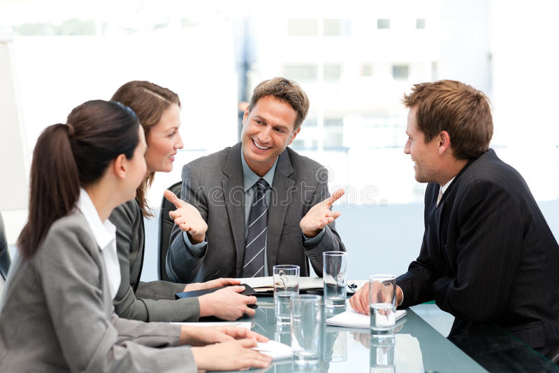 Delighted manager talking to his team at a table stock photos