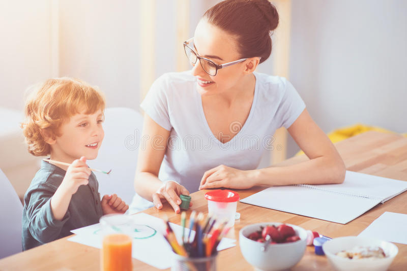 Delighted mother drawing with her toddler son together royalty free stock photography