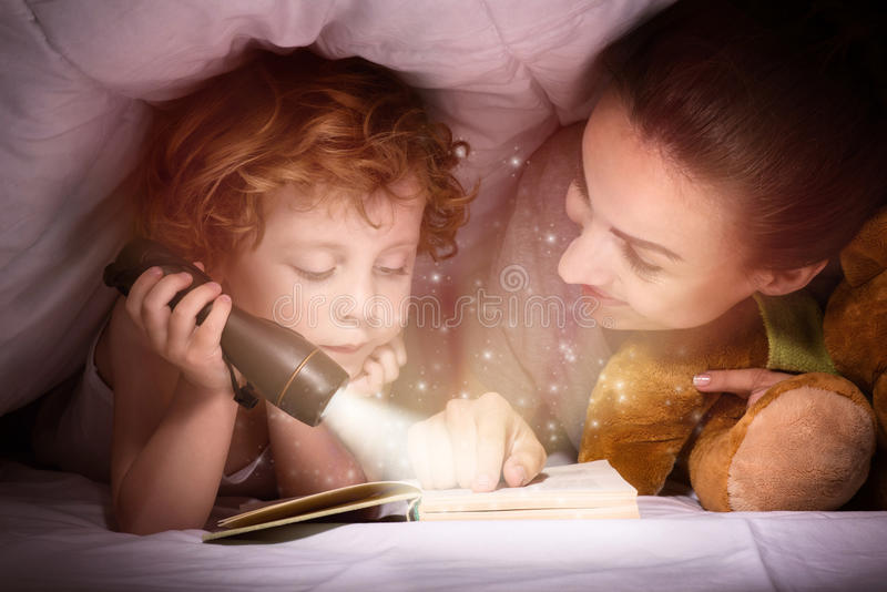 Delighted mother and son enjoying book before sleeping. Time for stories. Delighted happy cute mother and son enjoying a book before sleeping and using a stock image