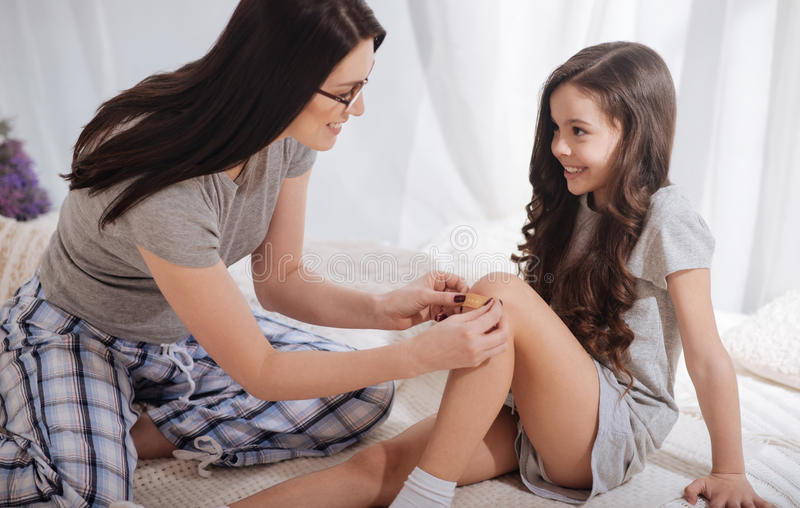 Delighted mother taking care of little daughters wound at home royalty free stock photo