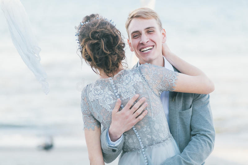 Delighted newly-weds cuddling at the seashore stock photography