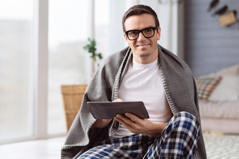 Delighted nice man holding a tablet royalty free stock images