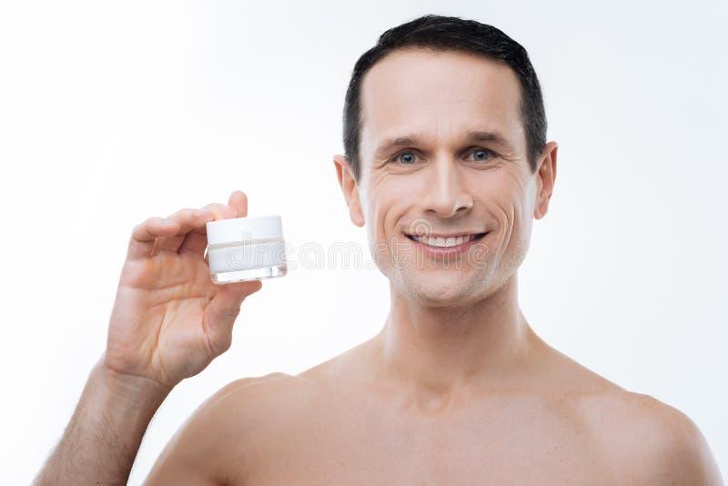 Delighted nice man using facial cosmetics royalty free stock photos