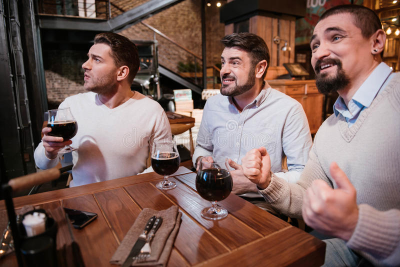 Delighted nice men watching football game stock photo