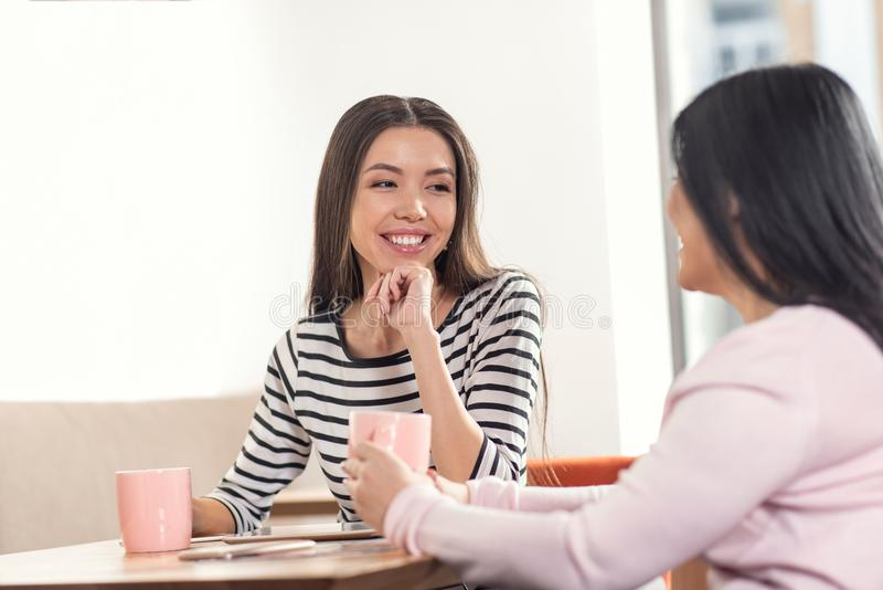 Delighted nice women talking. Meeting of friends. Delighted nice positive women looking at each other and talking while meeting in the cafeteria stock image