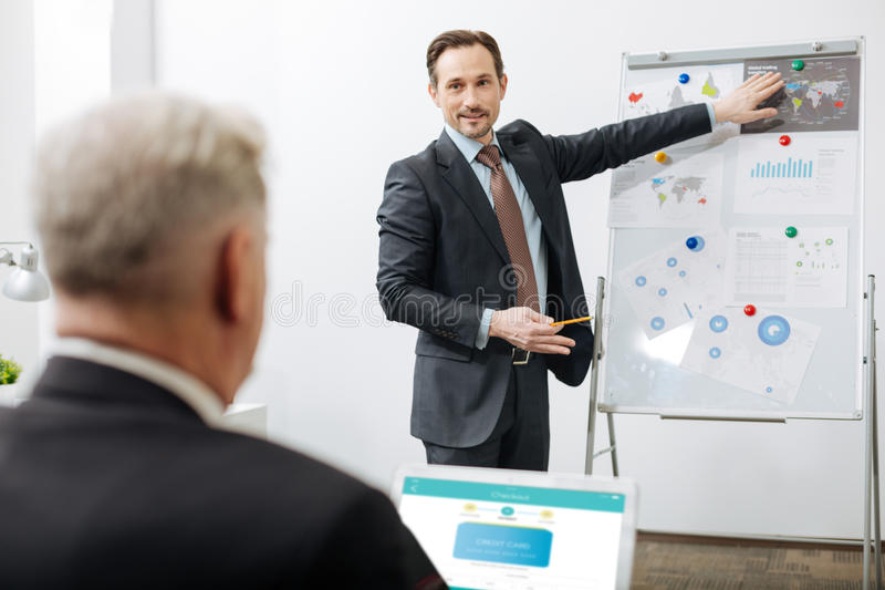 Delighted office manager representing the project at work. Delightful process of representing project. Delighted creative inventive manager standing near the royalty free stock image