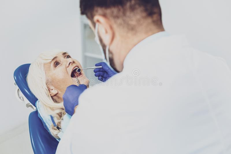 Delighted pensioner sitting with opened mouth. Do not worry. Competent medical worker wearing sterile uniform while treating his visitor royalty free stock photos