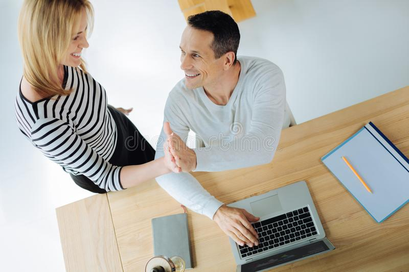 Delighted positive colleagues giving each other high five. This is success. Delighted positive cheerful colleagues smiling and giving each other a high five royalty free stock photo