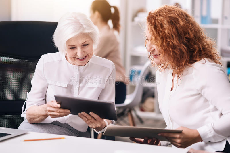 Delighted positive colleagues working in the office. Sharing creative points of view. Smiling delighted lively colleagues sitting in the business center and royalty free stock image
