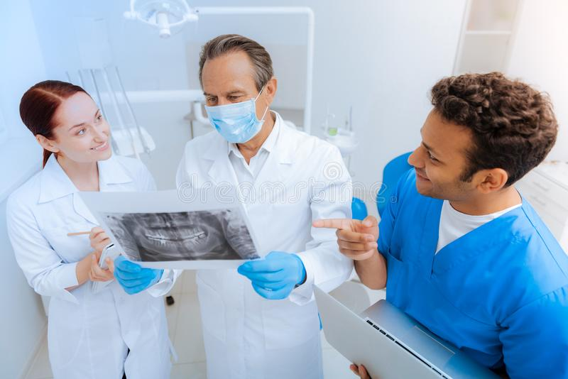 Delighted positive dentists discussing an X ray photo. Preliminary diagnosis. Delighted nice positive dentists standing together and discussing an X ray photo royalty free stock image