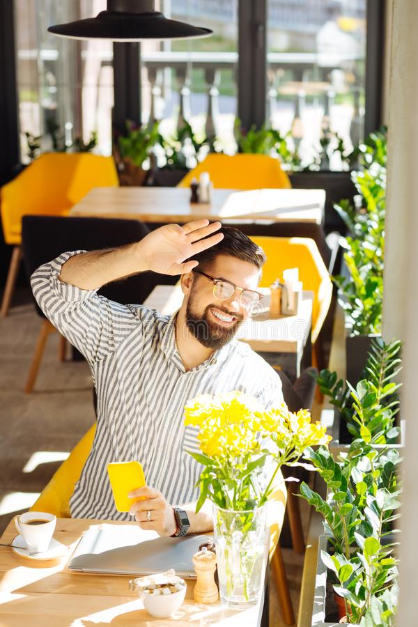 Delighted positive man looking into the window royalty free stock photography