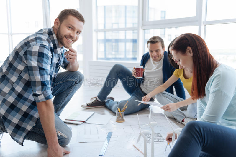 Delighted positive man sitting with his colleagues. Interesting project. Delighted positive handsome men sitting with his colleagues and smiling while working on stock images