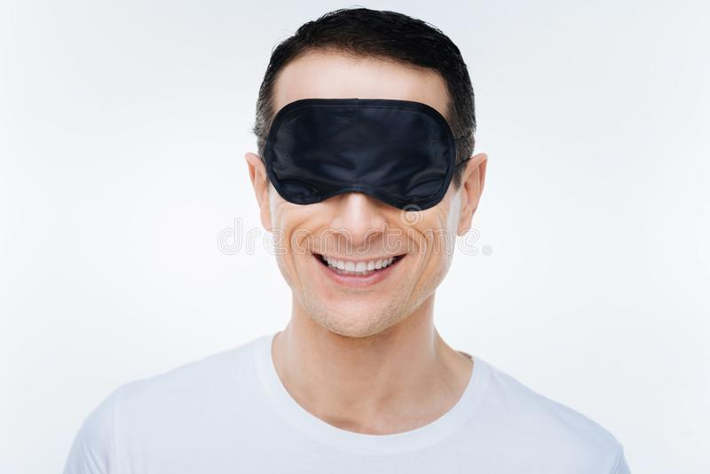 Delighted positive man wearing a sleeping mask royalty free stock image