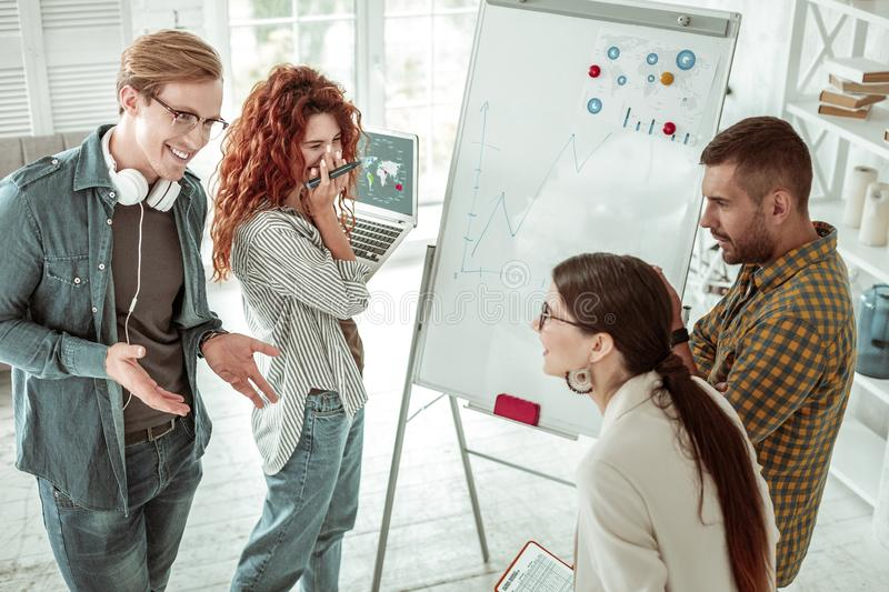 Delighted positive smart people enjoying working together stock photos
