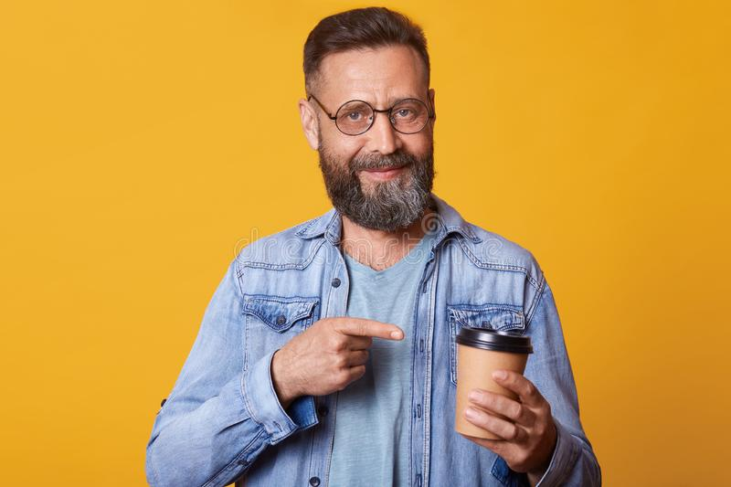 Delighted positive smiling handsome guy holding papercup of strong coffee in one hand, pointing at it with forefinger, having royalty free stock photography