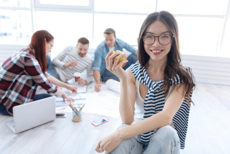 Delighted positive woman having an apple in her hands royalty free stock photos
