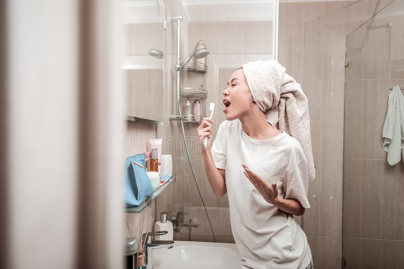 Delighted positive woman singing in the bathroom royalty free stock photos