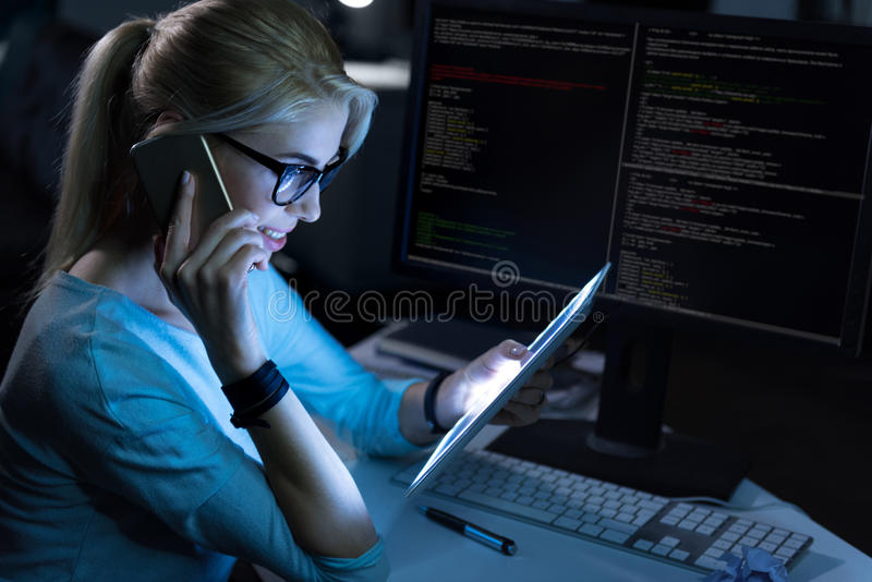 Delighted receptionist working in the dark lighted placement stock images