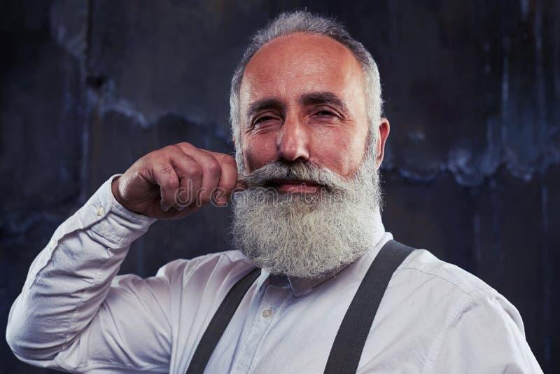Delighted senior man twirling beard stock images