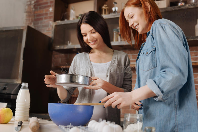 Delighted smiling girls looking at sieve. Always smile. Two friendly women wearing casual clothes sifting flour for pastry standing in semi position in the stock images