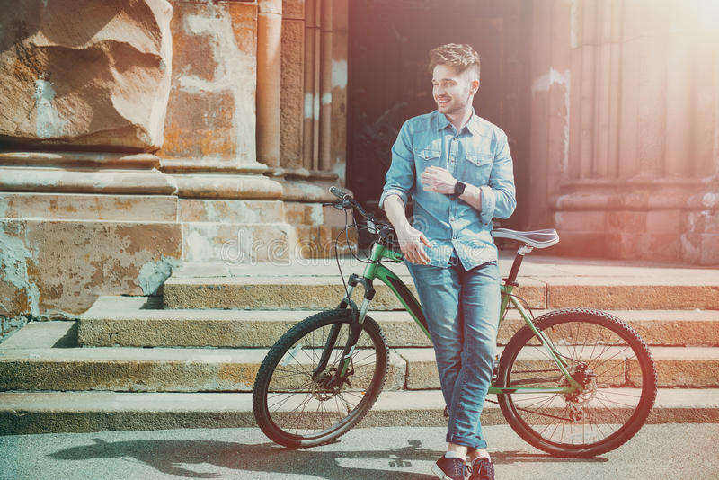 Delighted smiling man standing near bicycle stock image
