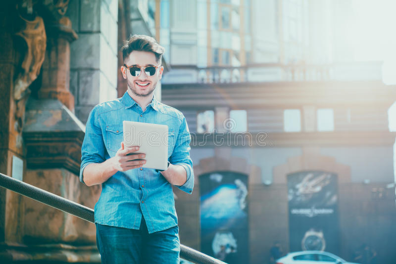 DElighted smiling young man using tablet stock images