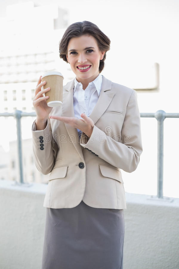 Delighted stylish brown haired businesswoman showing her coffee royalty free stock photos