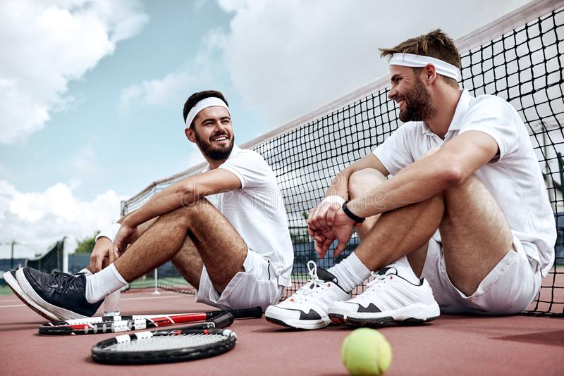 Delighted with the success. Men sit on the court talking to each other stock photos