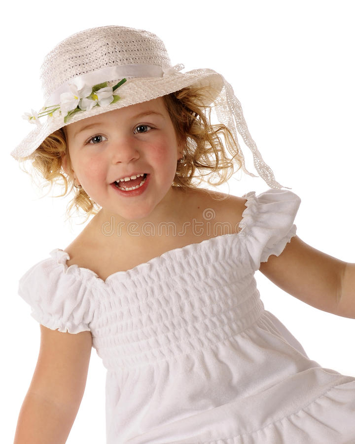 Delighted in a White Easter Bonnet. A beautiful preschooler delighted with her white Easter bonnet and dress stock photography