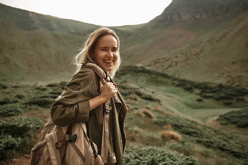 Delighted woman laughing while traveling in the mountains stock images