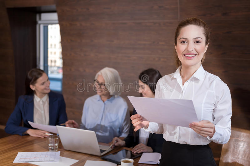 Delighted woman posing in office with documents and colleagues. Happy to work here. Delighted young pretty women posing and holding documents while her royalty free stock images