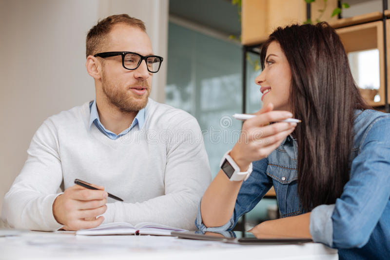Delighted young colleagues talking to each other. Discussing a project. Delighted nice young colleagues talking to each other and smiling while discussing their royalty free stock photos