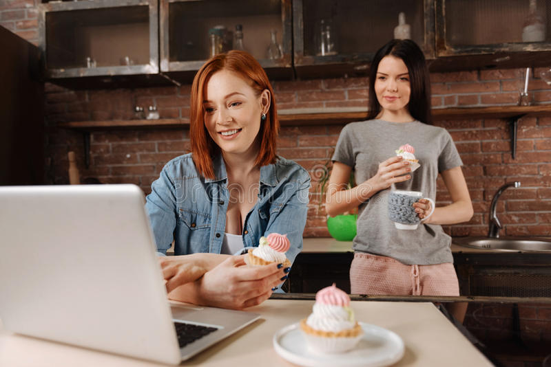 Delighted young females eating desserts. Have lunch. Two attractive smiling women holding cakes in their hands standing in the kitchen watching something on the stock photos
