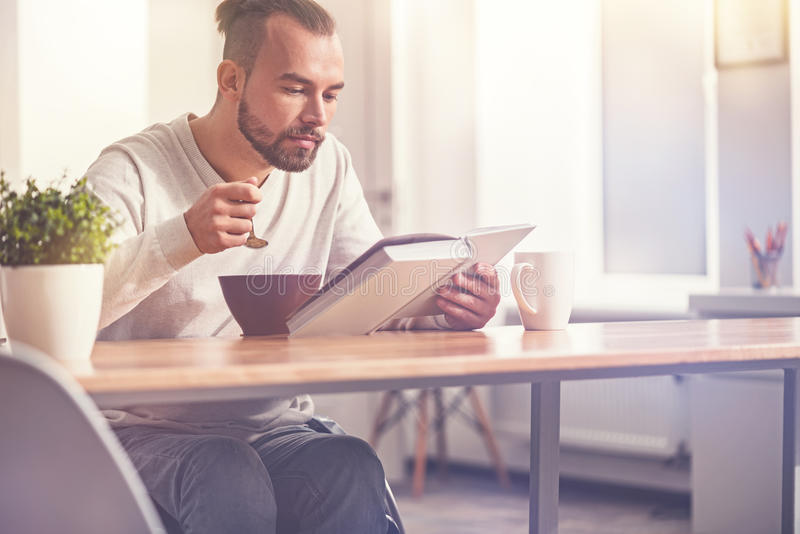 Delighted young man having breakfast royalty free stock photo