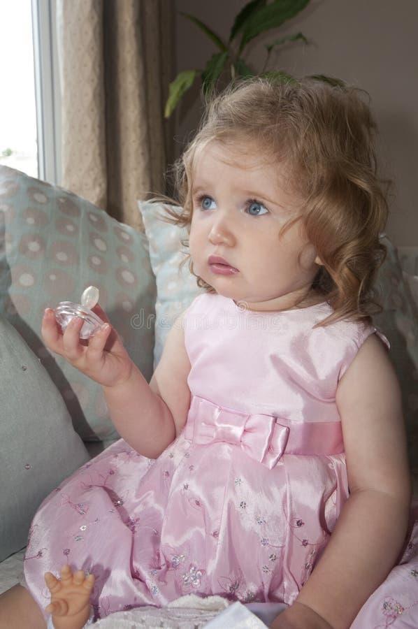 Delightful baby girl with dummy. stock photos