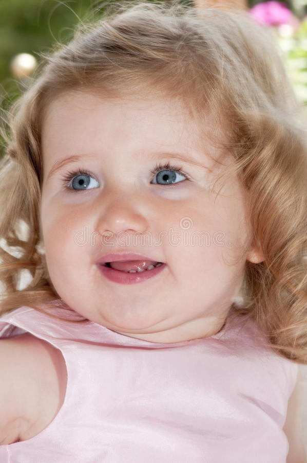 Delightful baby girl, smiling, with blue eyes. stock images