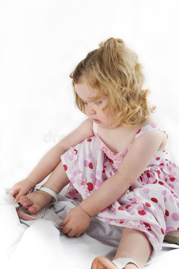 Delightful baby girl untying her shoe. stock photo