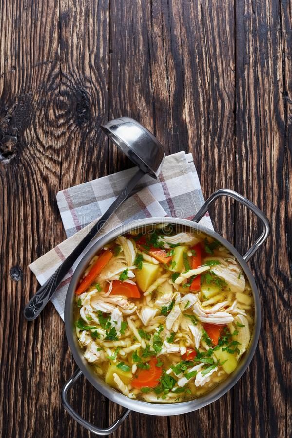 Delightful Chicken and vegetable hearty soup. Shredded Chicken breast and vegetable hearty soup with pasta in a metal casserole on an old rustic wooden table royalty free stock image