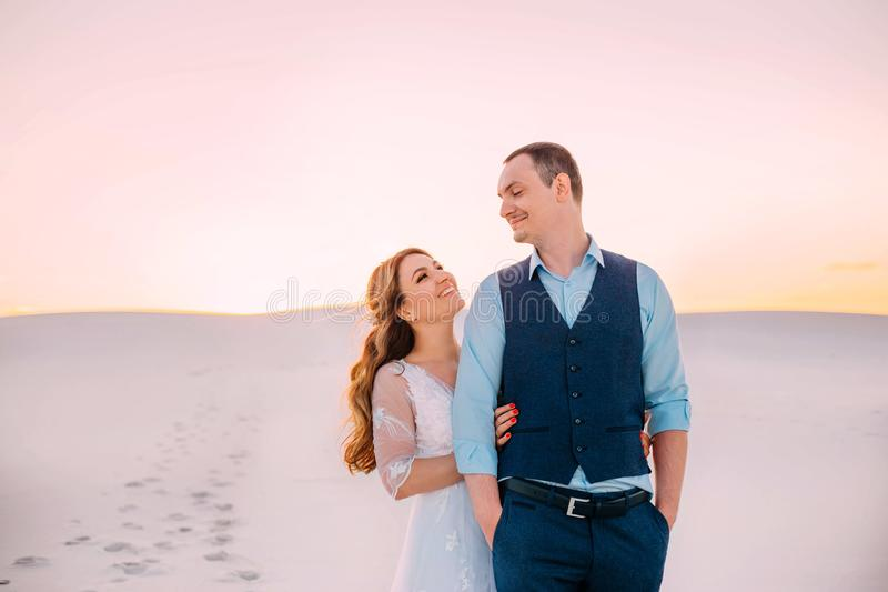 Delightful family couple in the desert of sand, the bride and groom smile at each other, happy wedding moments, a girl royalty free stock image