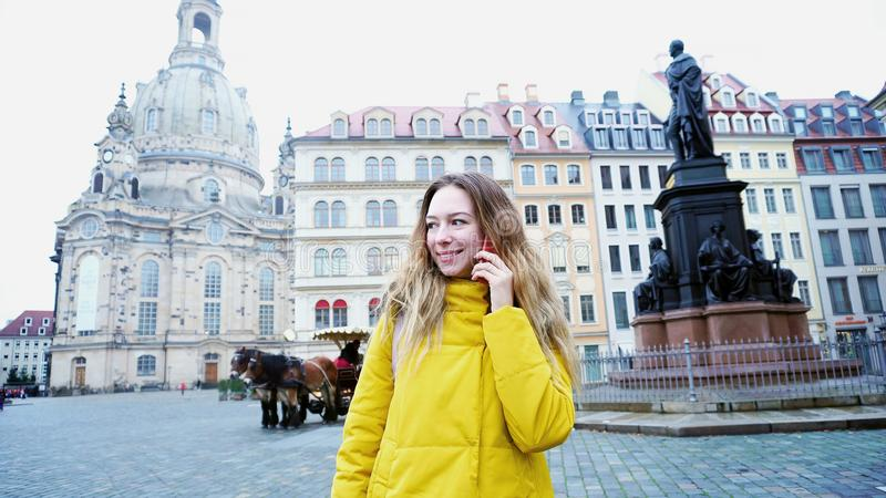 Alluring girl chatting on phone and walking in European city Dre royalty free stock images