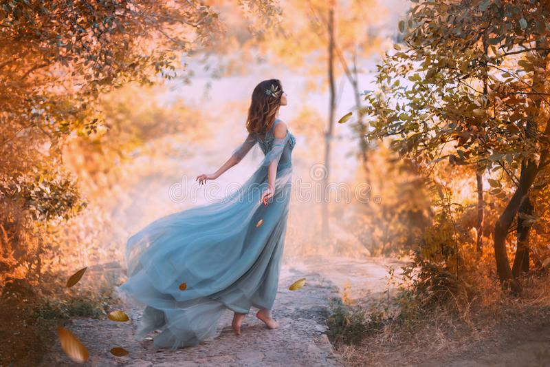Delightful light girl in sky blue turquoise dress with long flying train. Princess of wind and daughter of storm, lady with dark hair throws fallen leaves to royalty free stock images