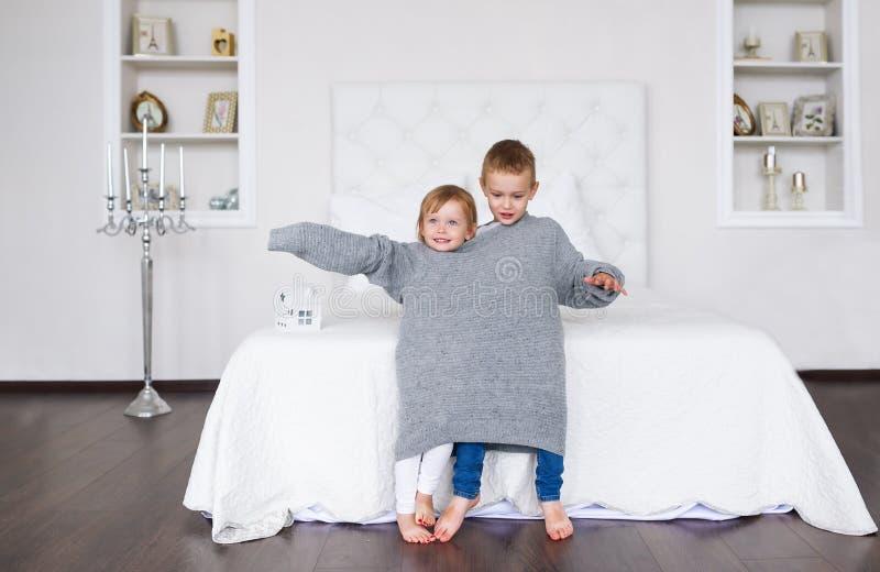 Delightful little children in big grey sweater. Delightful little children in big grey sweater royalty free stock image