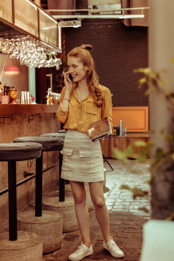 Delightful woman standing at bar and talking on the phone royalty free stock images