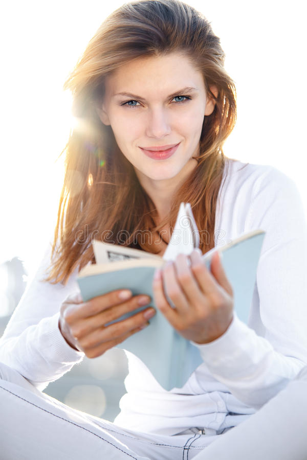 Delightful young woman holds the book. Smiling brunette girl in a bright clothing holding a book in her hands stock photo