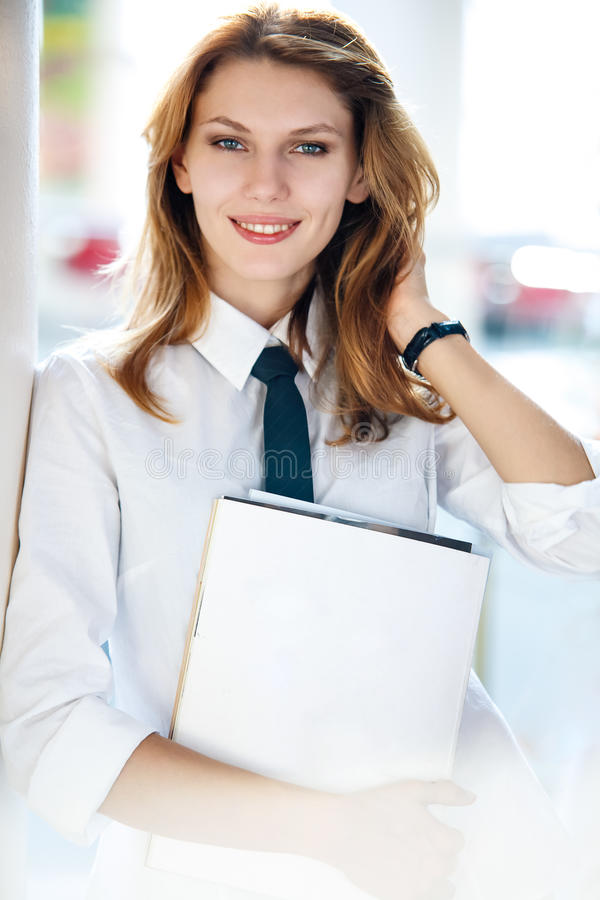 Delightful young woman holds the folder. Smiling brunette girl in a shirt with a tie holding folder with documents stock photography