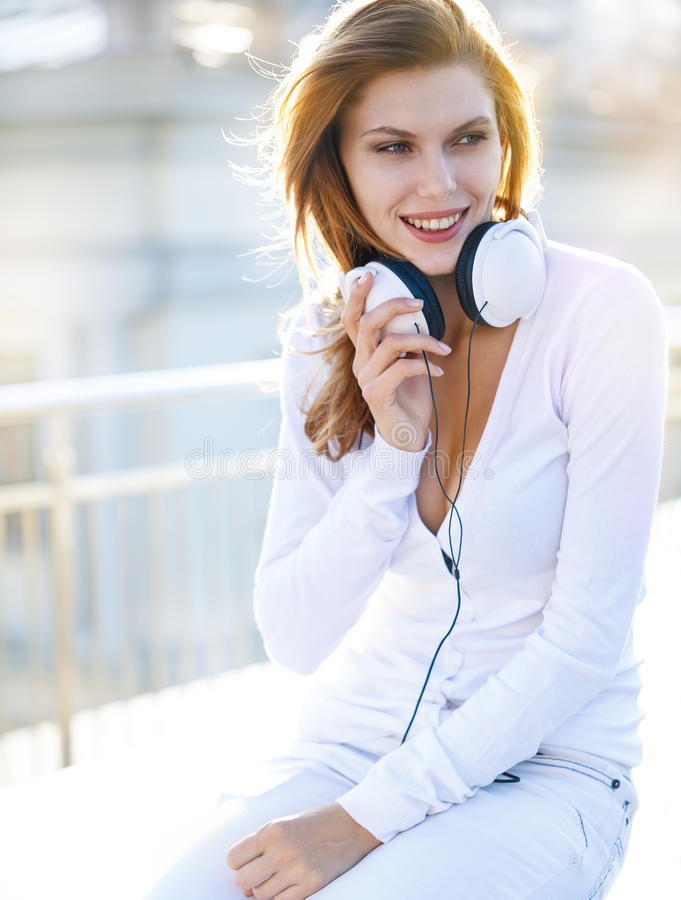 Delightful young woman holds the headphones. Smiling brunette girl in a bright clothing with white headphones looking to the side stock photo